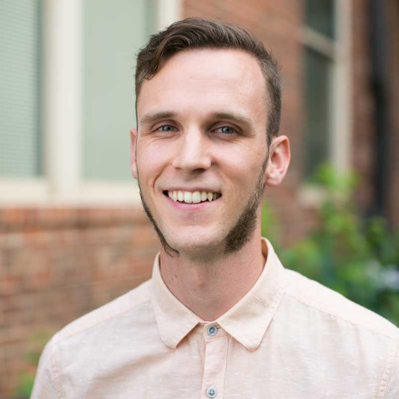 A photo of Corey Light, a smiling person wearing a light-peach button-up shirt